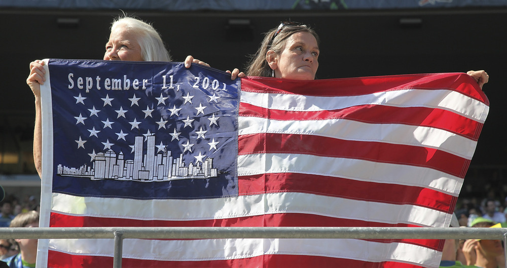 SEATTLE - SEPTEMBER 10:  Fans hold an American flag in remembrance of 9/11 during the game between the Seattle Sounders FC and Real Salt Lake at CenturyLink Field on September 10, 2011 in Seattle, Washington. (Photo by Otto Greule Jr/Getty Images)
