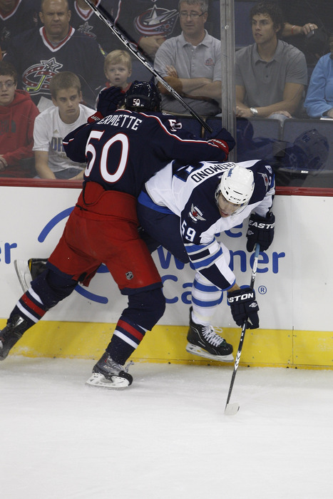 COLUMBUS, OH - SEPTEMBER 20:  Antoine Vermette #50 of the Columbus Blue Jackets checks Zach Redmond #59 of the Winnipeg Jets during their game on September 20, 2011. (Photo by John Grieshop/Getty Images)