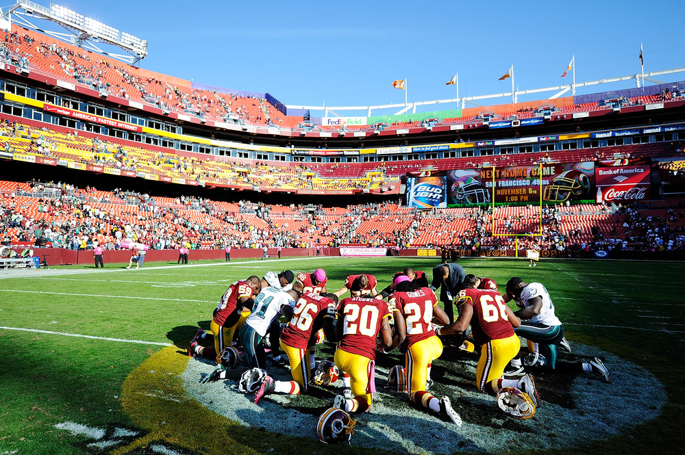 LANDOVER, MD - OCTOBER 16:  Members of the Washington Redskins and Philadelphia Eagles pray at midfield after a game at FedExField on October 16, 2011 in Landover, Maryland.  (Photo by Patrick McDermott/Getty Images)