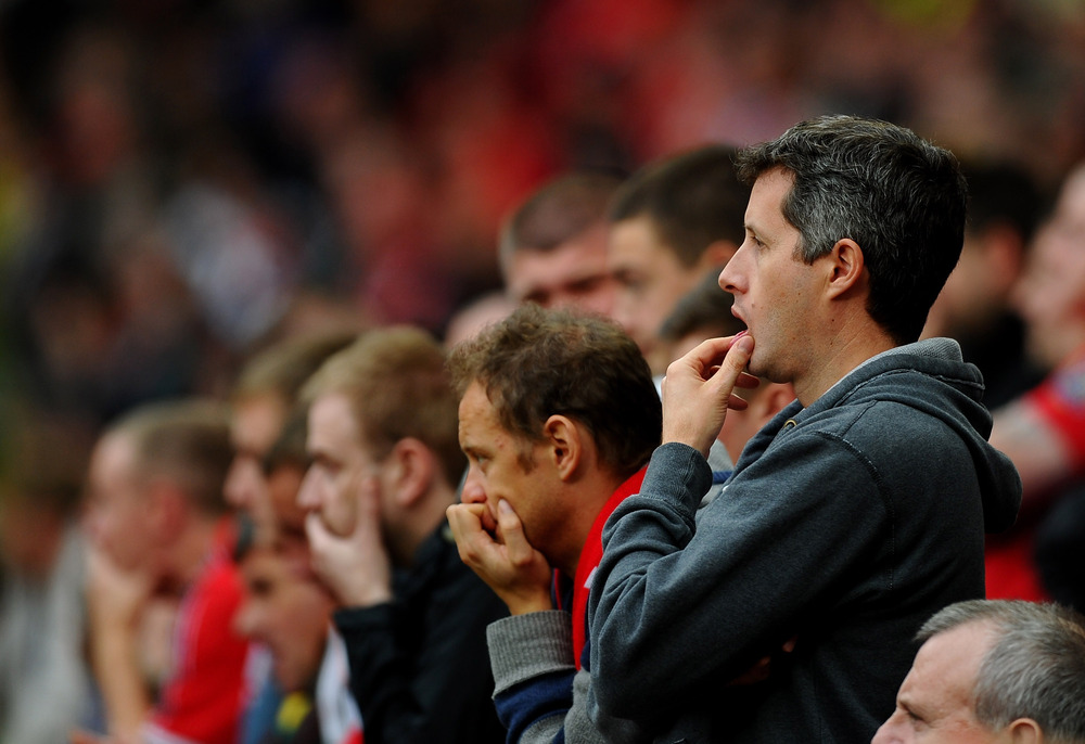 Manchester United fans look dejected during the Barclays Premier League match between Manchester United and Manchester City at Old Trafford.