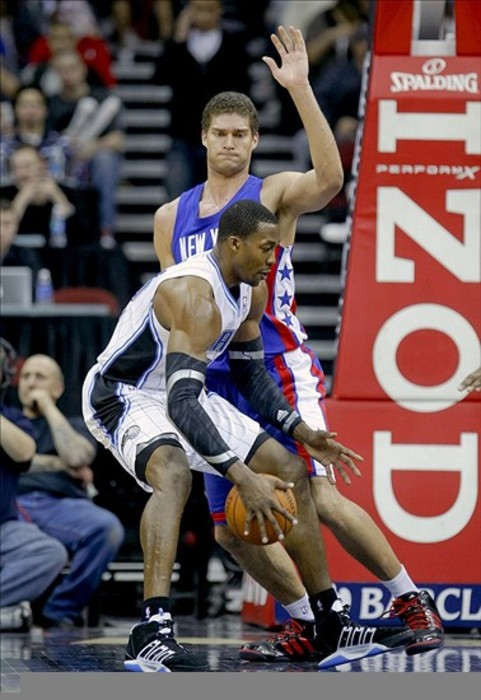Feb 22, 2012; Newark, NJ, USA;  Orlando Magic center Dwight Howard (12) is defended by New Jersey Nets center Brook Lopez (11) at the Prudential Center. Orlando Magic defeat the New Jersey Nets 108-91. Mandatory Credit: Jim O'Connor-US PRESSWIRE