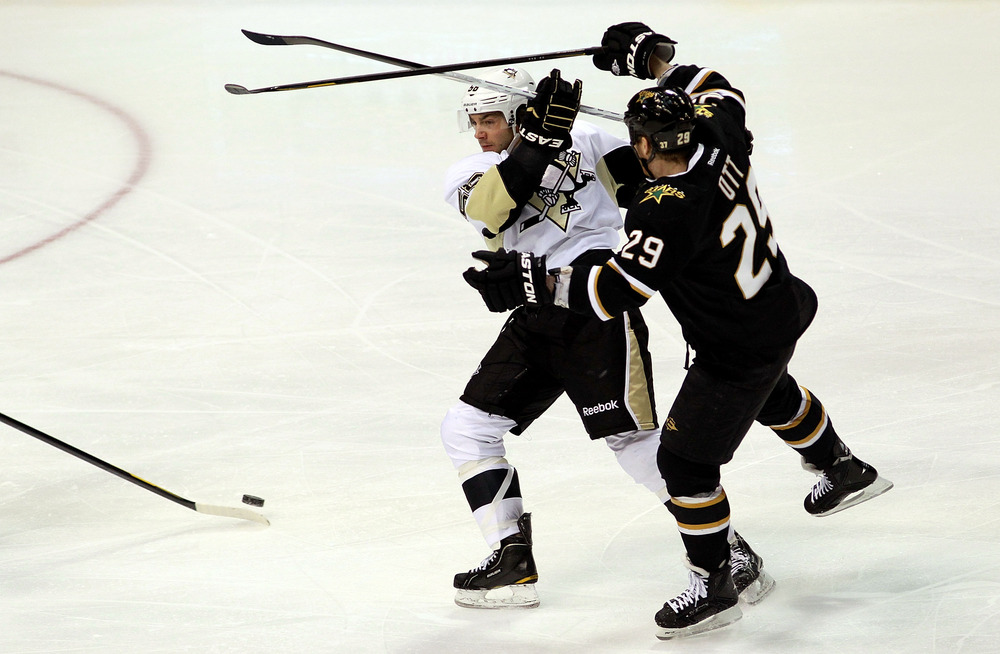 DALLAS, TX - FEBRUARY 29:  Kris Letang #58 of the Pittsburgh Penguins skates the puck with Steve Ott #29 of the Dallas Stars at American Airlines Center on February 29, 2012 in Dallas, Texas.  (Photo by Ronald Martinez/Getty Images)