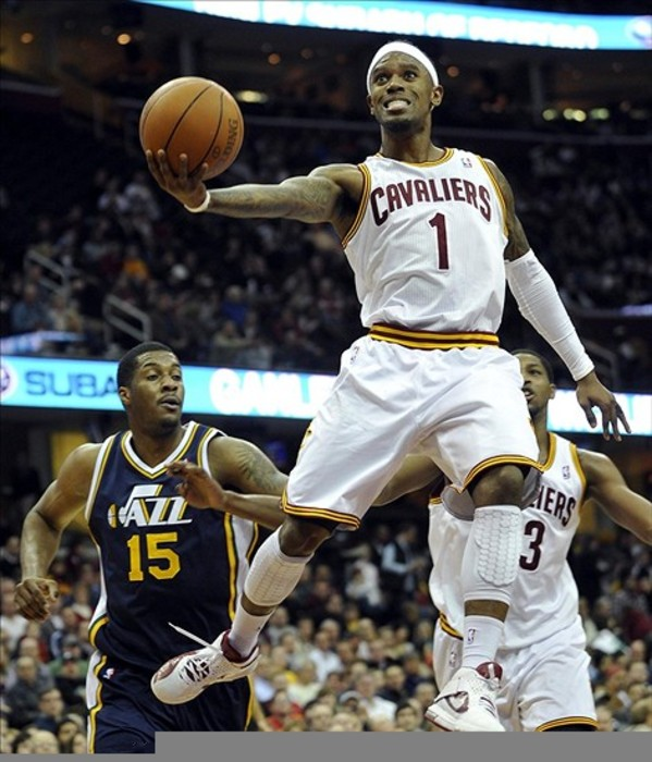 Mar 5, 2012; Cleveland, OH, USA; Cleveland Cavaliers shooting guard Daniel Gibson (1) makes a layup past Utah Jazz forward/center Derrick Favors (15) in the second quarter at Quicken Loans Arena. Mandatory Credit: David Richard-US PRESSWIRE