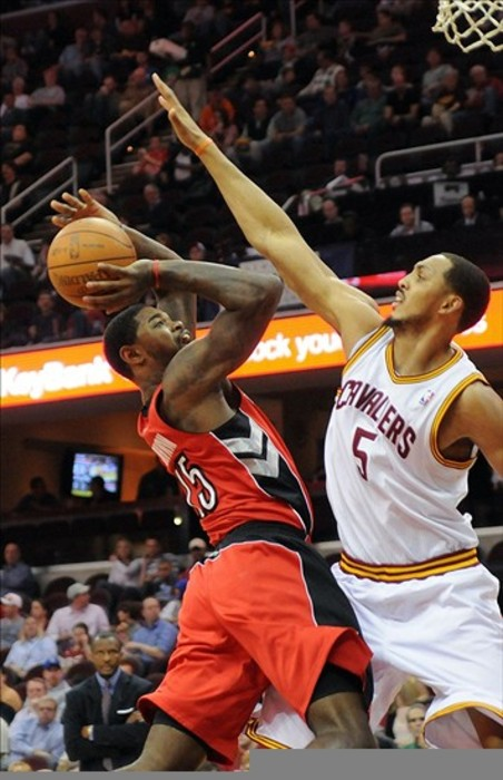 March 13, 2012; Cleveland, OH, USA: Toronto Raptors power forward Amir Johnson (15) goes up for a shot as Cleveland Cavaliers center Ryan Hollins (5) defends during the game at Quicken Loans Arena.  Mandatory Credit: Eric P. Mull-USPRESSWIRE