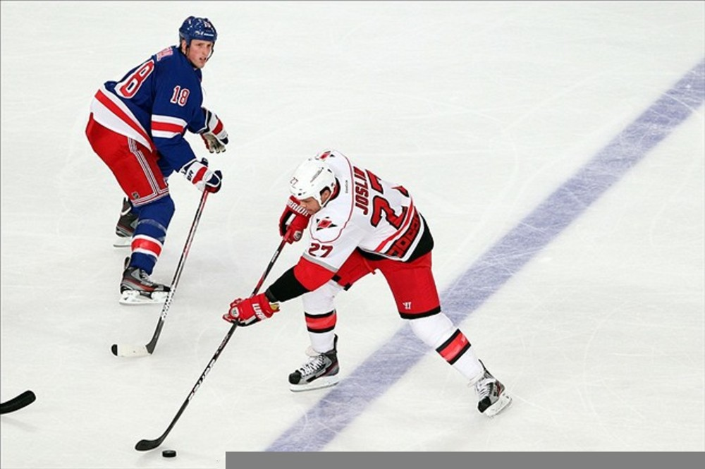 Mar 13 2012; New York, NY, USA;  Carolina Hurricanes defenseman Derek Joslin (27) steals the puck from New York Rangers defenseman Marc Staal (18) during the second period at Madison Square Garden.  Mandatory Credit: Anthony Gruppuso-US PRESSWIRE