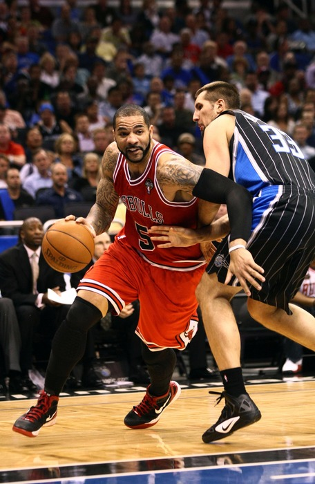 Mar 19, 2012; Orlando, FL, USA; Chicago Bulls power forward Carlos Boozer (5) drives around Orlando Magic power forward Ryan Anderson (33) during the first quarter at Amway Center. Mandatory Credit: Douglas Jones-US PRESSWIRE
