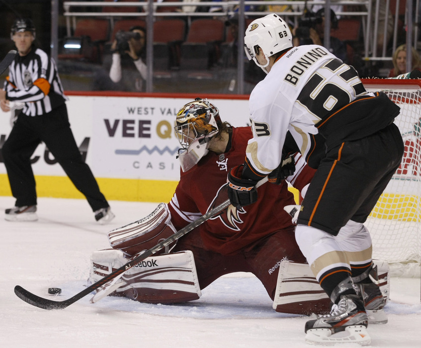 March 31, 2012; Glendale, AZ, USA; Phoenix Coyotes goalie Mike Smith (41) makes the save on Anaheim Ducks center Nick Bonino (63) in the first period at Jobing.com.  Mandatory Credit: Rick Scuteri-US PRESSWIRE