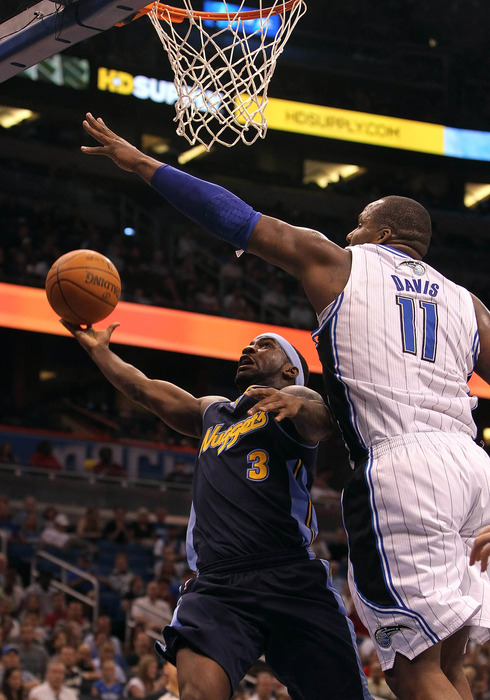 April 1, 2012; Orlando FL, USA; Denver Nuggets point guard Ty Lawson (3) shoots as Orlando Magic power forward Glen Davis (11) defends during the first half at Amway Center. Mandatory Credit: Kim Klement-US PRESSWIRE