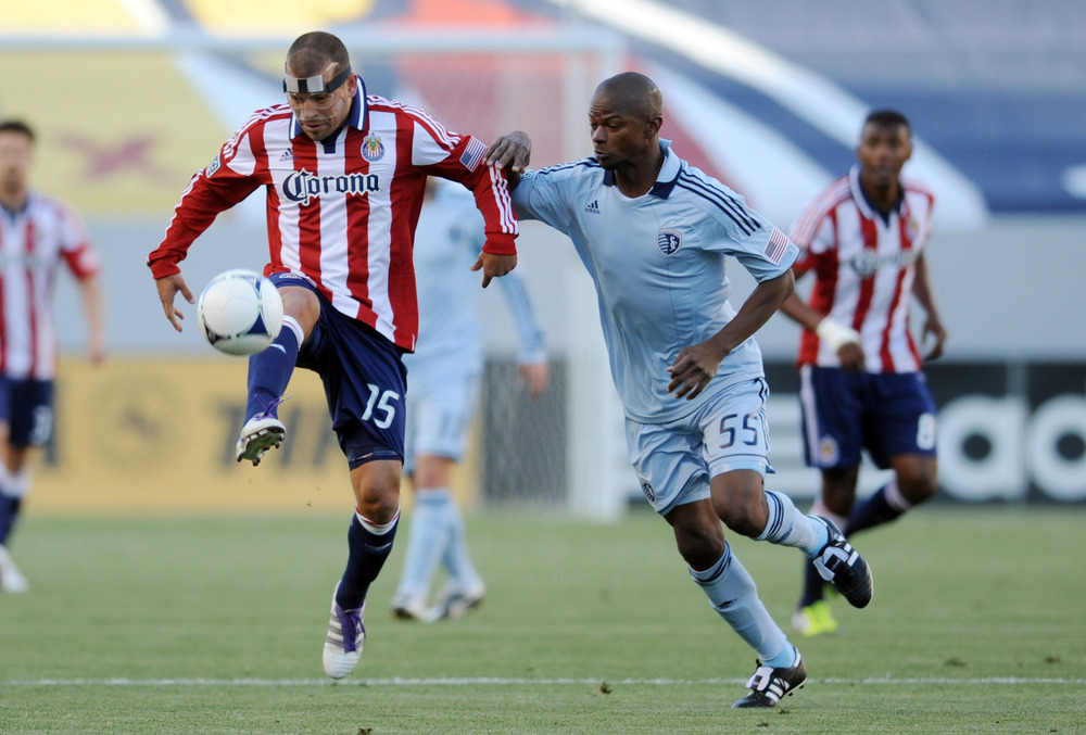 Apr 1, 2012; Carson, CA, USA; Chivas USA forward Alejandro Moreno (15) passes the ball defended by Sporting Kansas City defenseman Julio Cesar (55) during the first half at the Home Depot Center. Mandatory Credit: Kelvin Kuo-US PRESSWIRE