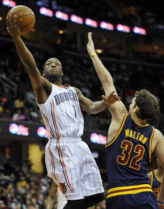 Apr 10, 2012; Cleveland, OH, USA; Charlotte Bobcats point guard Kemba Walker (1) shoots while defended by Cleveland Cavaliers small forward Luke Walton (32) in the second quarter at Quicken Loans Arena. Mandatory Credit: David Richard-US PRESSWIRE