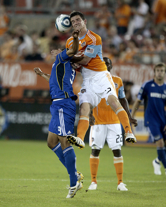 HOUSTON - MAY 01:  Bobby Boswell #32 of the Houston Dynamo goes over the back of Teal Bunbury #9 of the Kansas City Wizards at Robertson Stadium on May 1, 2010 in Houston, Texas.  (Photo by Bob Levey/Getty Images)