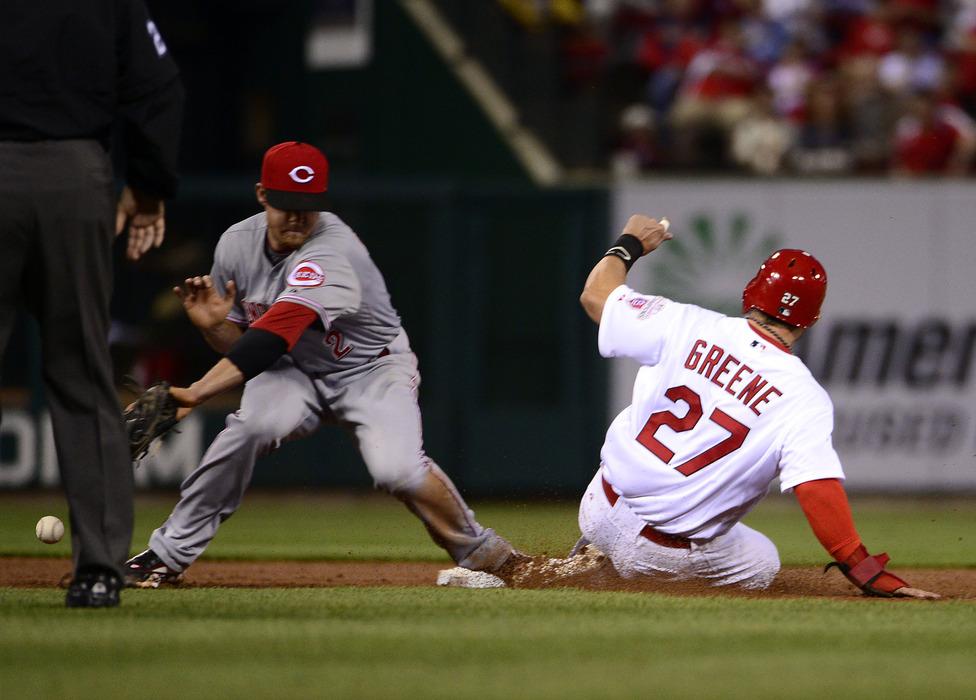 April 18, 2012; St. Louis, MO, USA; St. Louis Cardinals second baseman Tyler Greene (27) steals second base as Cincinnati Reds shortstop Zack Cozart (2) drops the ball at Busch Stadium. Mandatory Credit: Scott Rovak-US PRESSWIRE
