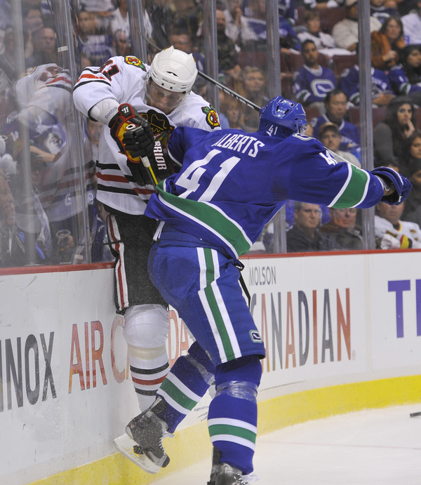 Is this a hit, or is Hossa just trying to squeeze through? (Photo by Rich Lam/Getty Images)