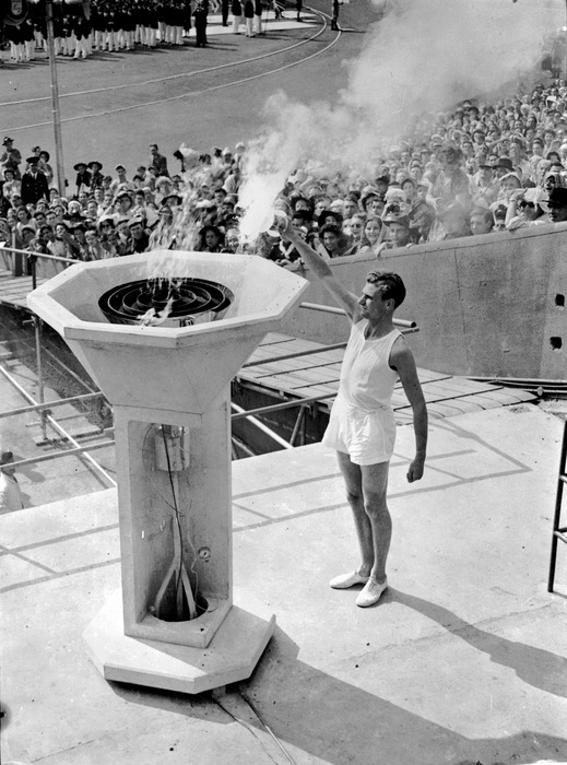 May 1948: A British athlete bears the Olympic Torch into the Empire Stadium at Wembley, London, and inaugurates the 1948 Olympic Games by lighting the ceremonial flame.  (Photo by PNA Rota/Getty Images)