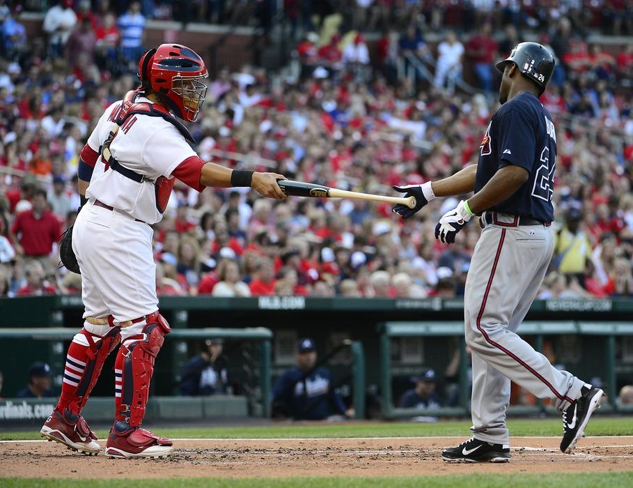 May 12, 2012; St. Louis, MO, USA; St. Louis Cardinals catcher Yadier Molina (4) hands Atlanta Braves center fielder Michael Bourn (24) his bat after a foul ball at Busch Stadium. Mandatory Credit: Scott Rovak-US PRESSWIRE