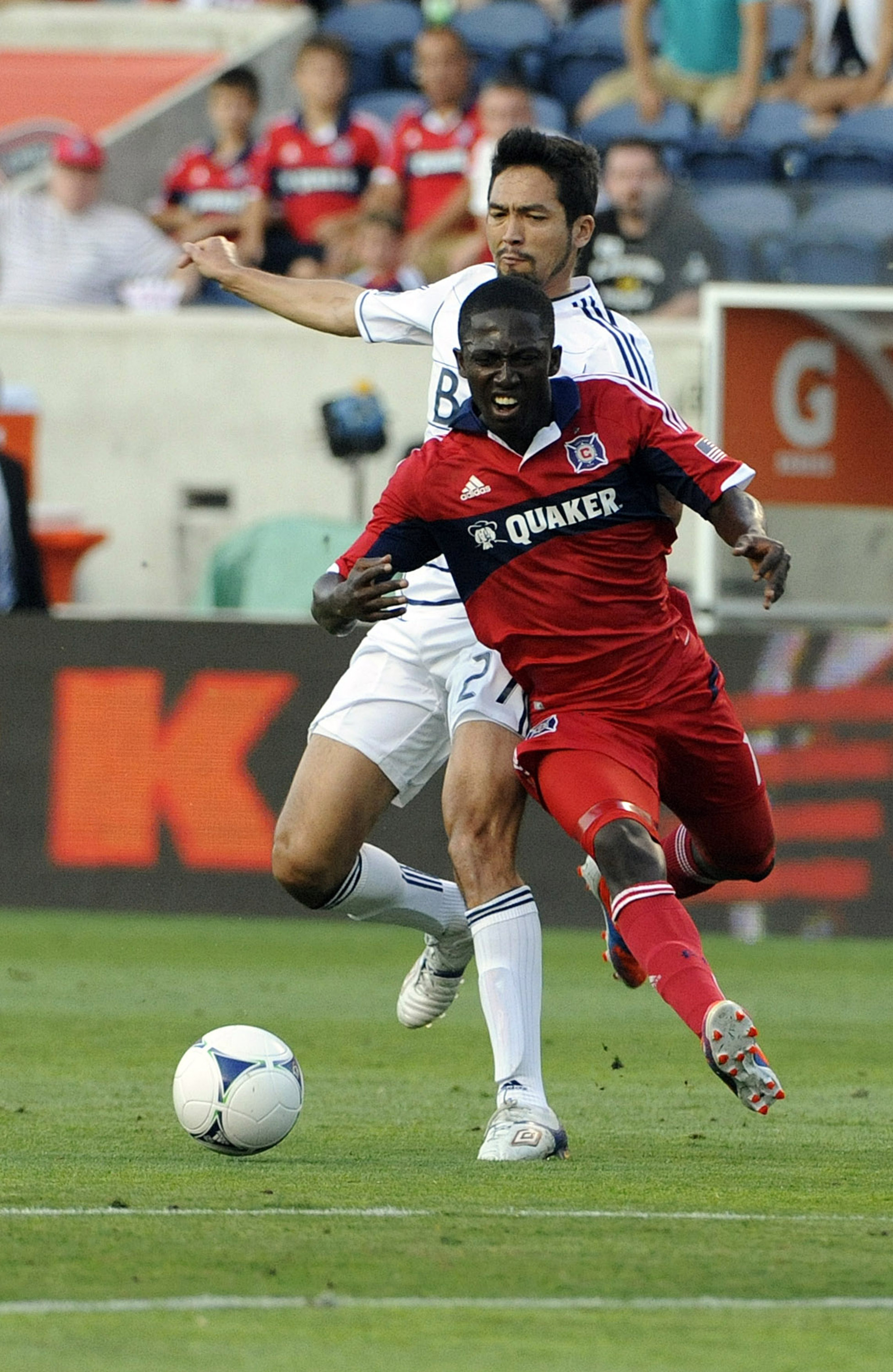 BRIDGEVIEW, IL - JULY 14: Patrick Nyarko #14 of the Chicago Fire is defended by Jun Marques Davidson #27 of the Vancouver Whitecaps in an MLS match on July 14, 2012 at Toyota Park in Bridgeview, Illinois.   (Photo by David Banks/Getty Images)