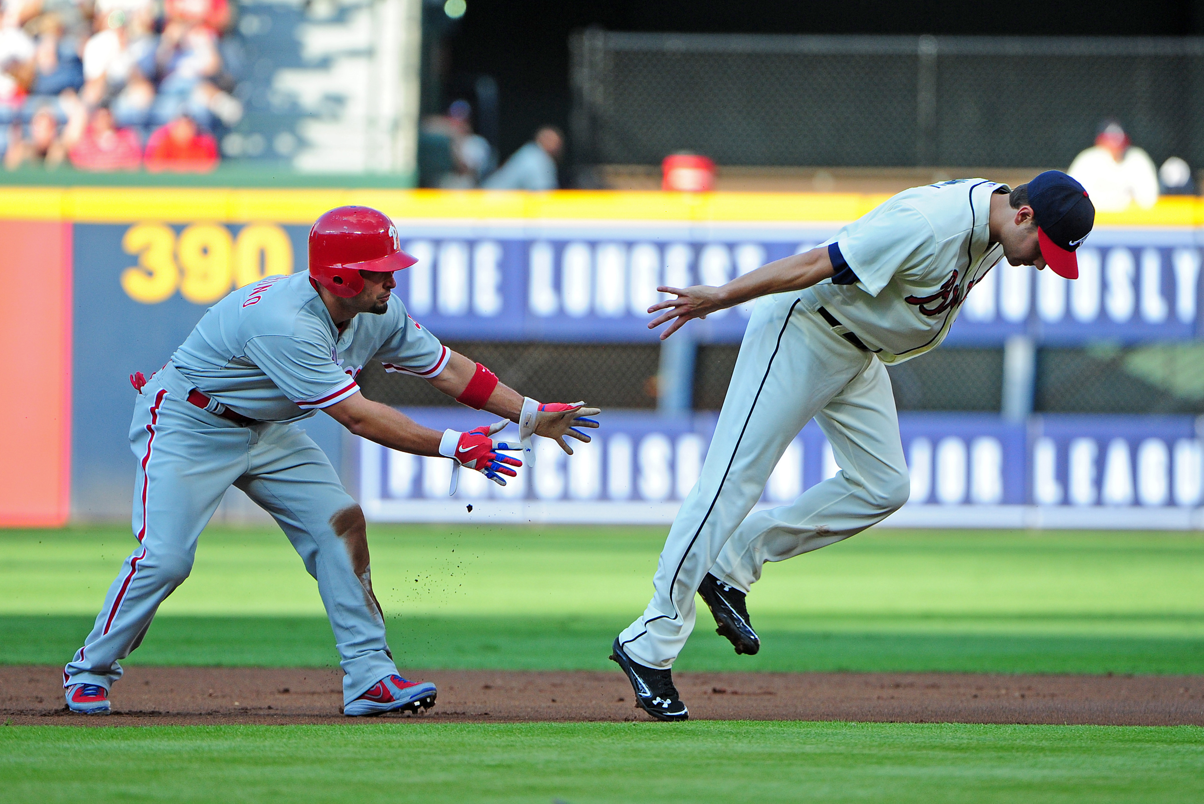 ATLANTA, GA: Paul Janish #4 of the Atlanta Braves completes a double play against Shane Victorino #8 of the Philadelphia Phillies at Turner Field in Atlanta, Georgia. (Photo by Scott Cunningham/Getty Images)