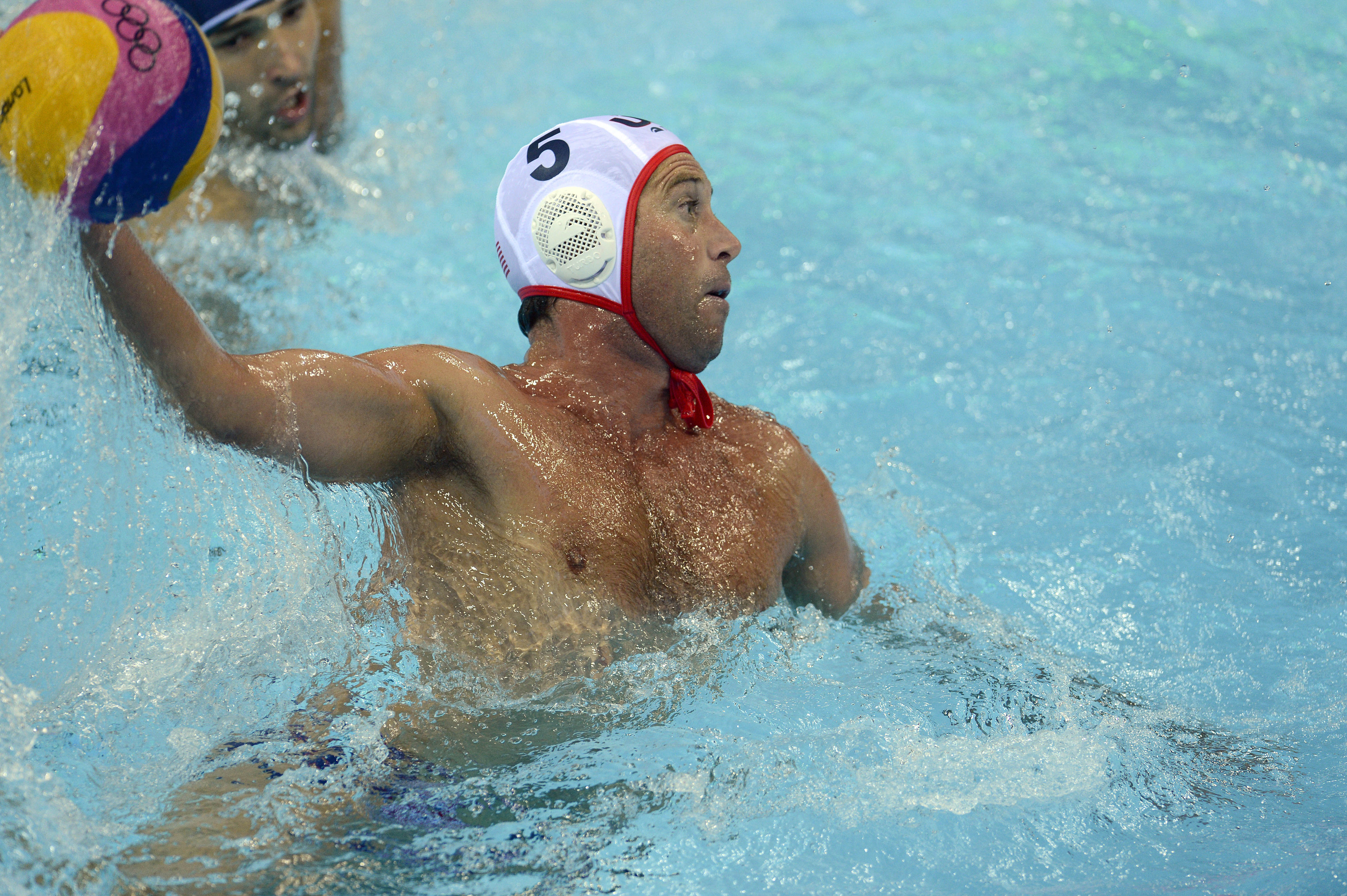 Jul 31, 2012; London, United Kingdom; USA driver Adam Wright (5) throws the ball against Romania during the London 2012 Olympic Games at Water Polo Arena. Mandatory Credit: John David Mercer-USA TODAY Sports