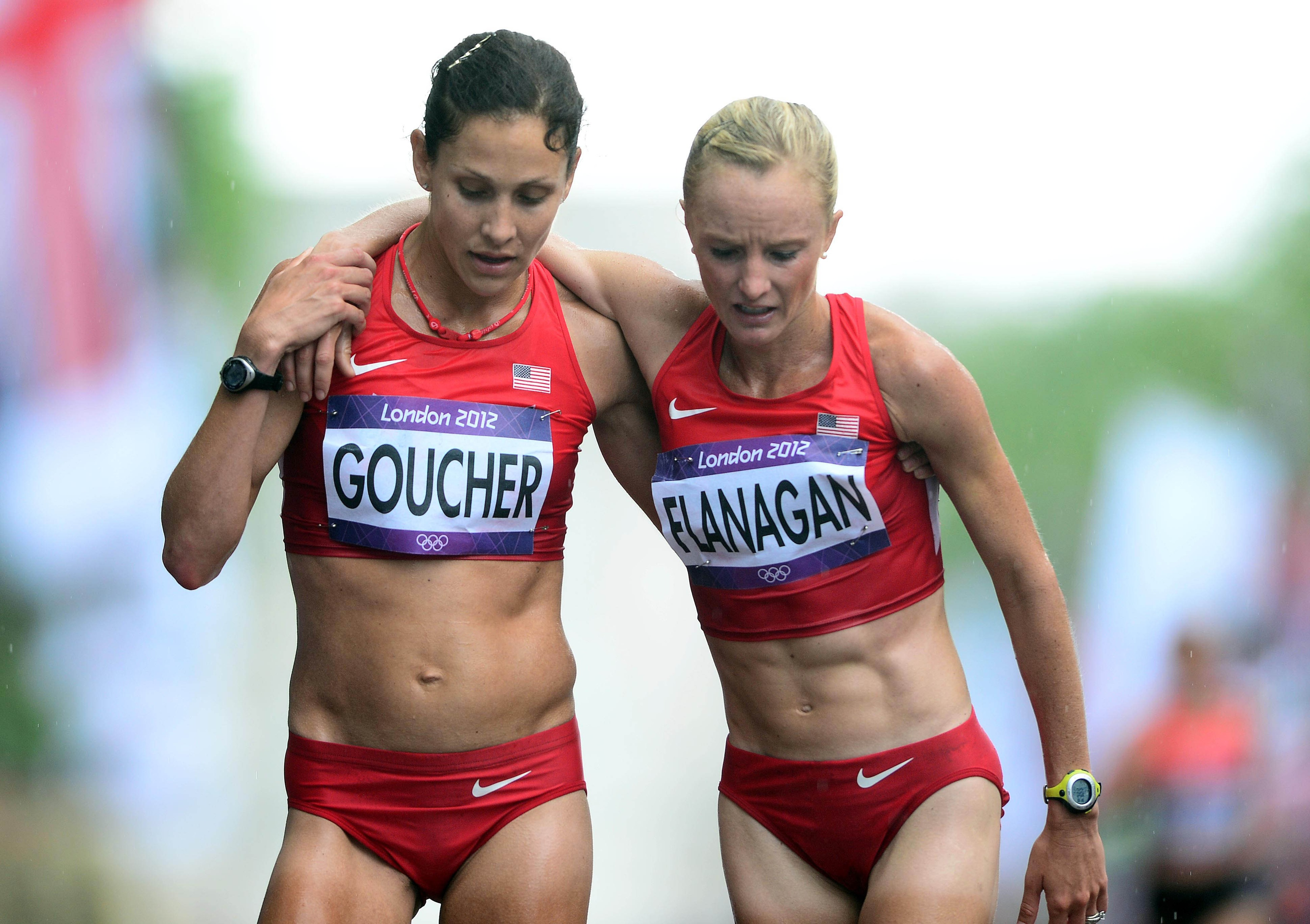 Aug 5, 2012; London, United Kingdom; Kara Goucher (USA), left, helps teammate Shalane Flanagan (USA) walk off the course following the women's marathon in the London 2012 Olympic Games at The Mall. Mandatory Credit: Andrew Weber-USA TODAY Sports