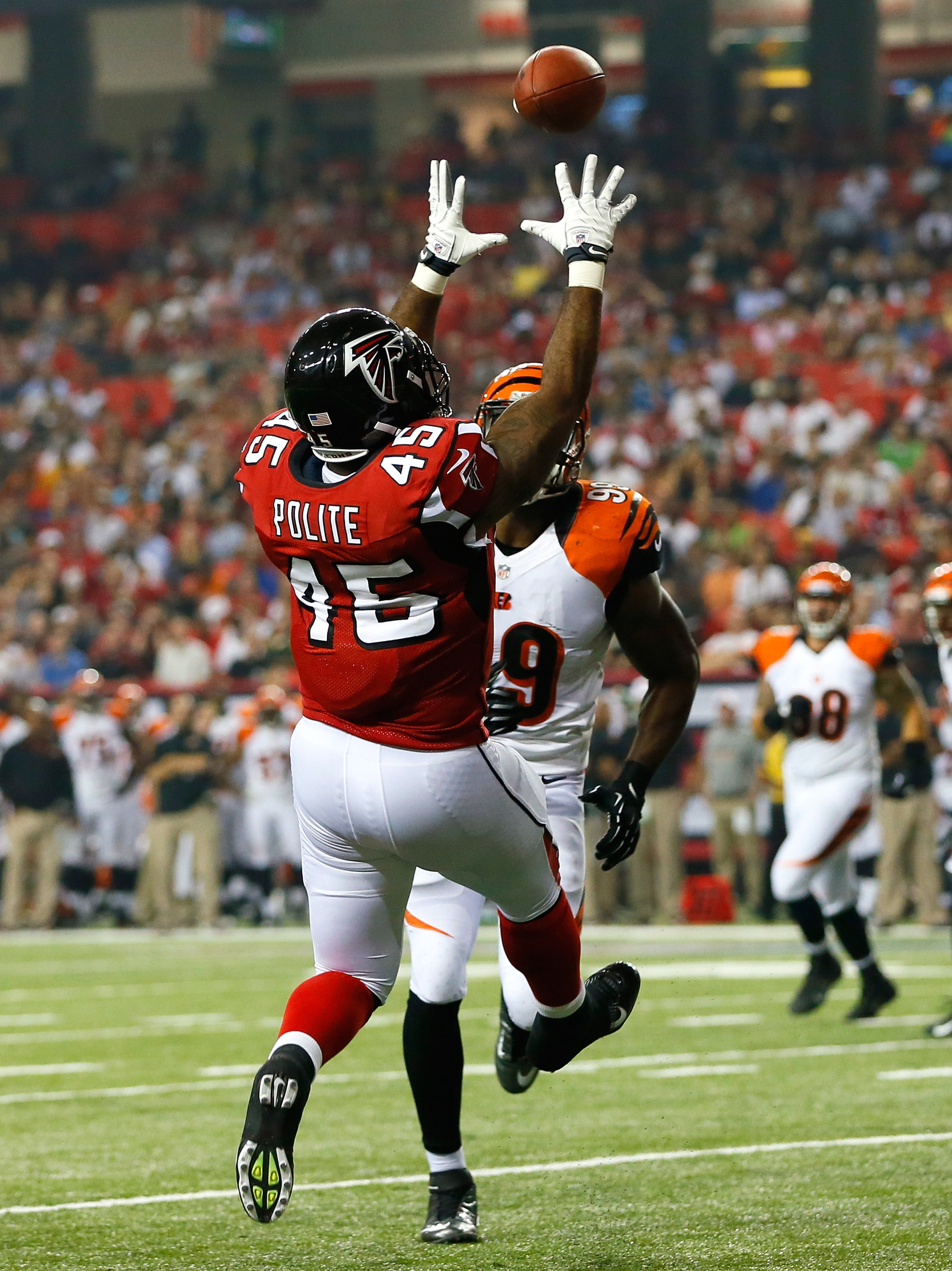 ATLANTA, GA - AUGUST 16:  Lousaka Polite #45 of the Atlanta Falcons pulls in this touchdown reception against Manny Lawson #99 of the Cincinnati Bengals at Georgia Dome on August 16, 2012 in Atlanta, Georgia.  (Photo by Kevin C. Cox/Getty Images)