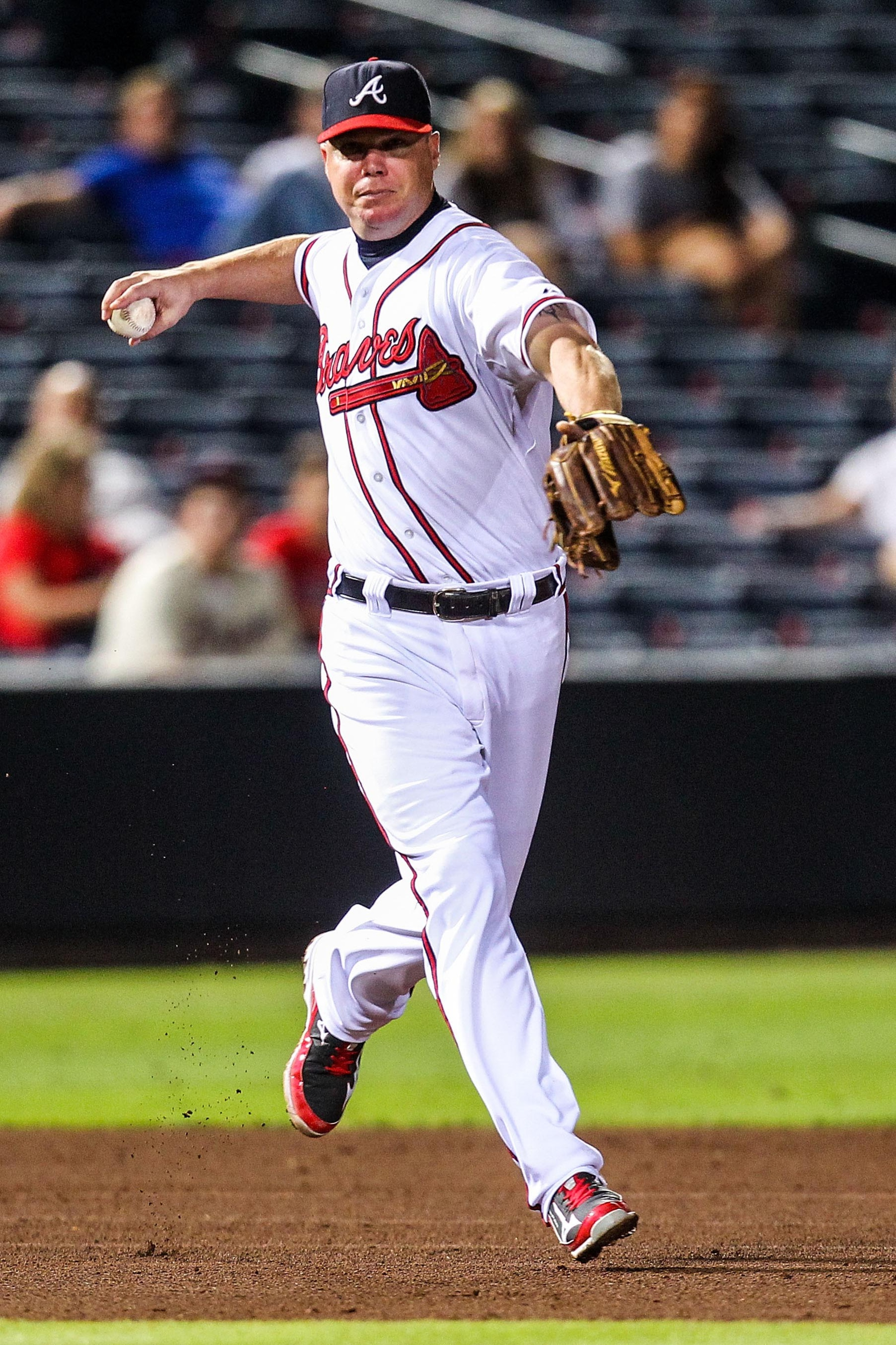 September 4, 2012; Atlanta, GA, USA; Atlanta Braves third baseman Chipper Jones (10) fields a ground ball for an out in the eighth inning against the Colorado Rockies at Turner Field. Mandatory Credit: Daniel Shirey-US PRESSWIRE