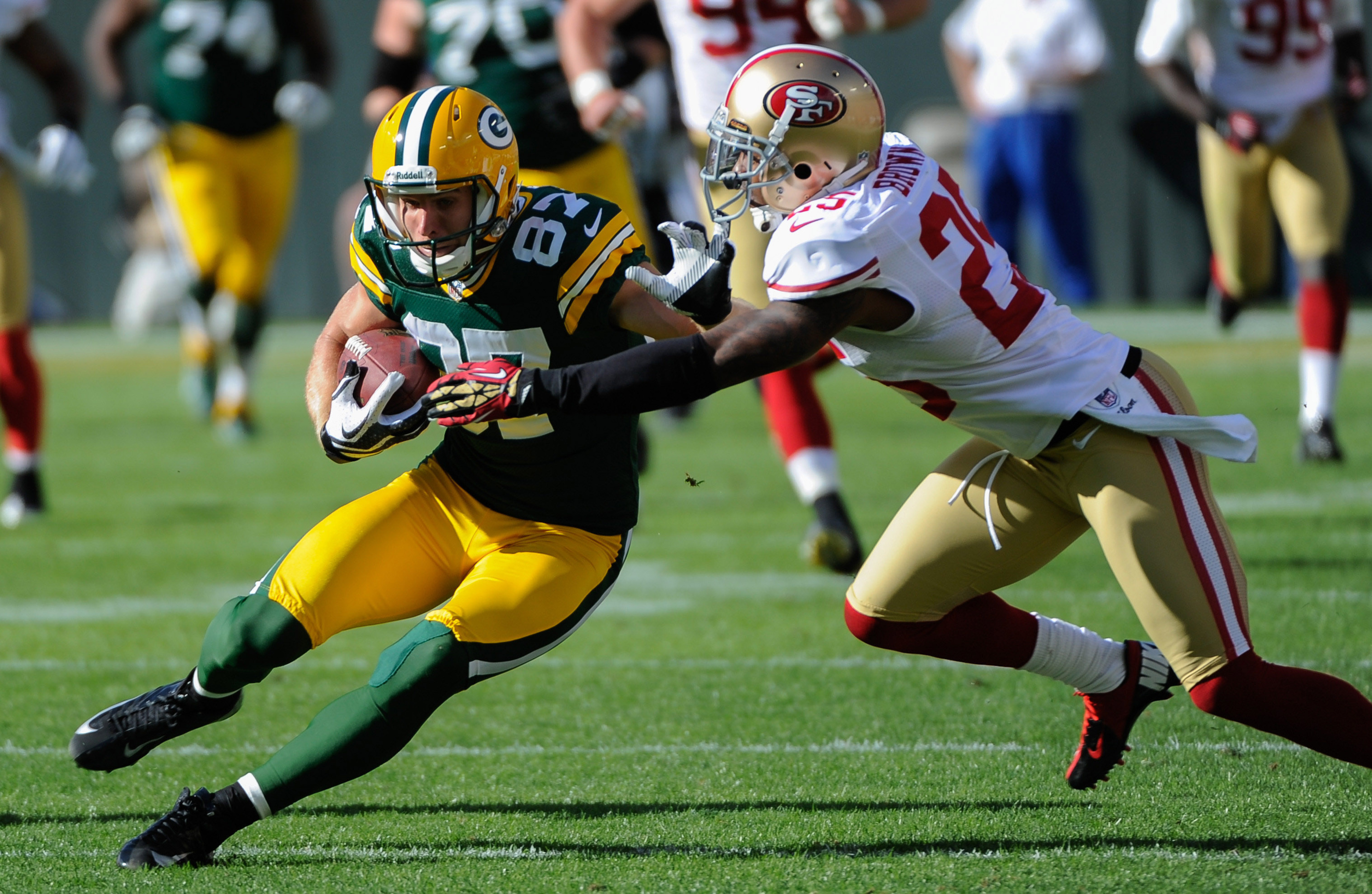Sept 9, 2012; Green Bay, WI, USA;   Green Bay Packers wide receiver Jordy Nelson (87) tries to break a tackle by San Francisco 49ers cornerback Tarell Brown (25) at Lambeau Field.  Mandatory Credit: Benny Sieu-US PRESSWIRE