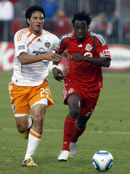 TORONTO - JULY 1: Amadou Sanyang #22 of Toronto FC battles for the ball with Brian Ching #25 of Houston Dynamo during a MLS game at BMO Field July 1 2010 in Toronto Ontario Canada. (Photo by Abelimages/Getty Images)