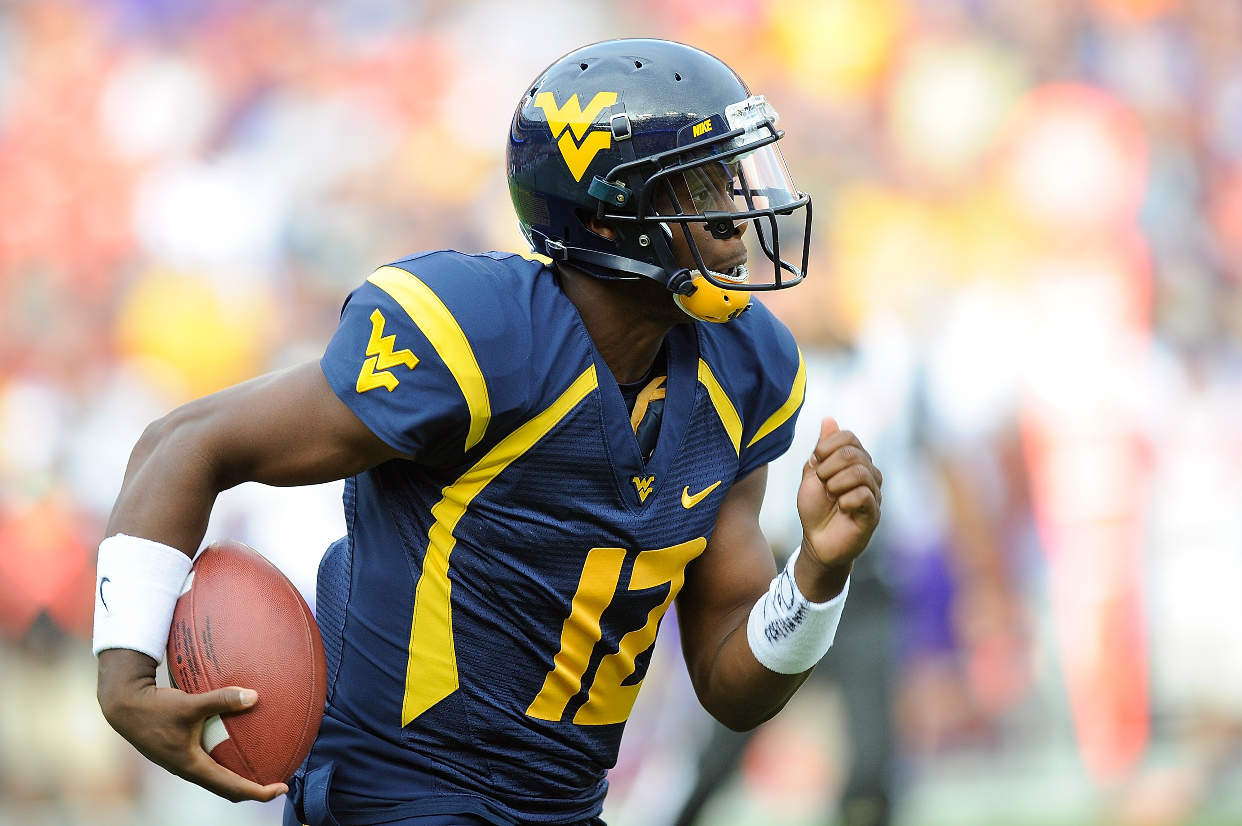 LANDOVER, MD - SEPTEMBER 15:  Geno Smith #12 of the West Virginia Mountaineers runs the ball against the James Madison Dukes during a game at FedExField on September 15, 2012 in Landover, Maryland.  (Photo by Patrick McDermott/Getty Images)