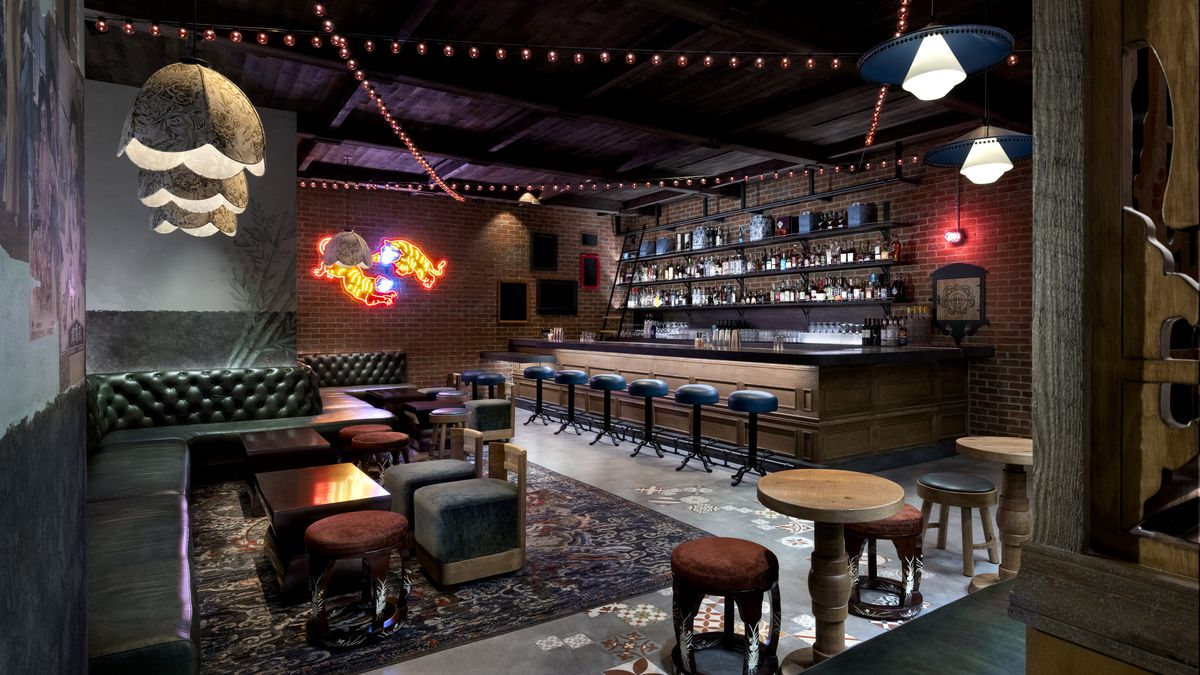 A speakeasy with a bar and neon tigers on a brick wall
