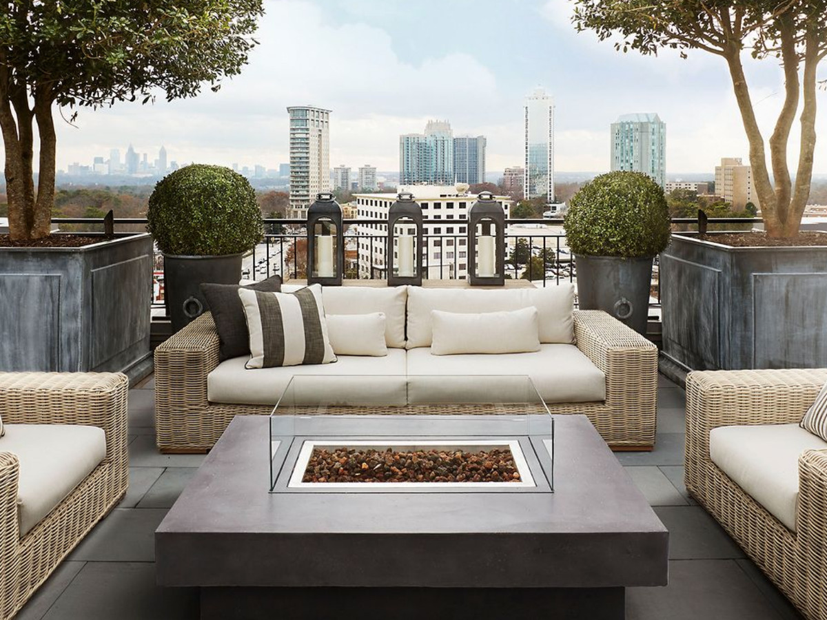 The roof of a store. There are couches, a fire pit, and trees in large planters. In the distance is a city skyline with many tall buildings.