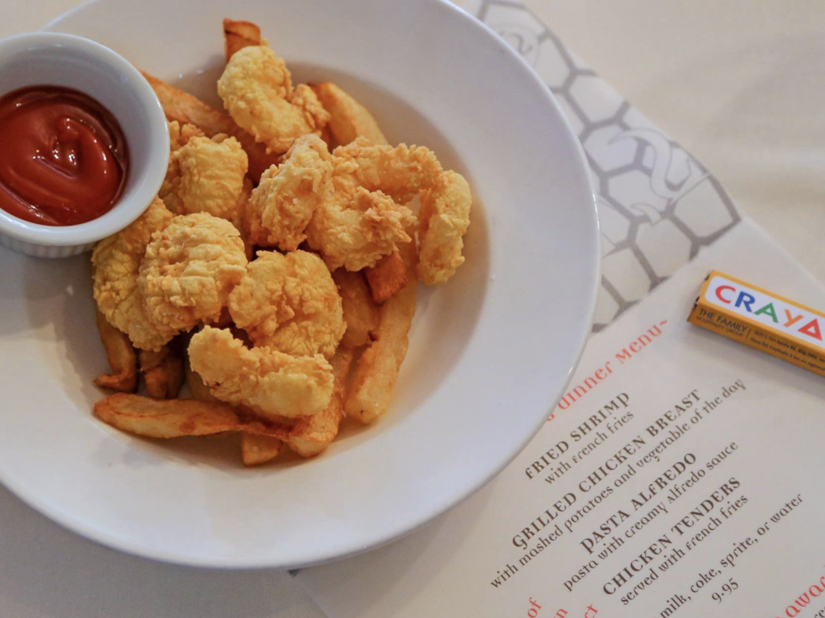 A bowl of fried shrimp sits next to a children's menu and crayons