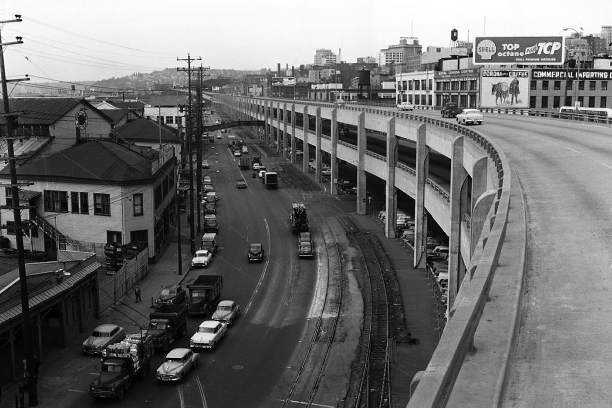 The Alaskan Way Viaduct spans over a road with adjacent houses and buildings. This is an old black and white photograph.