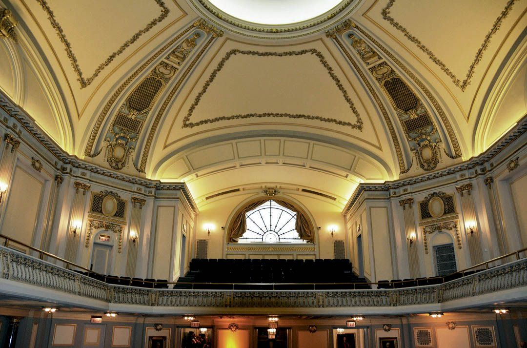 A domed-ceiling with ornate decorative molding. There is a skylight and balcony seating.