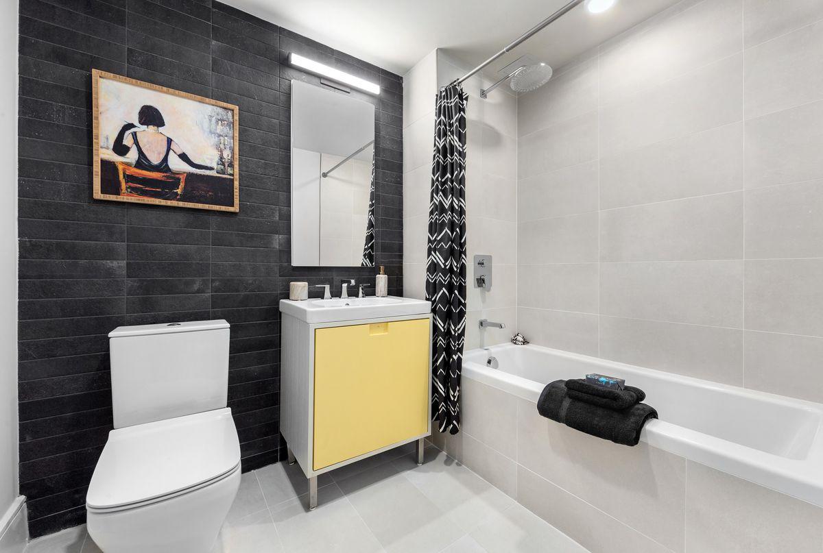 A bathroom with black wall tiles.