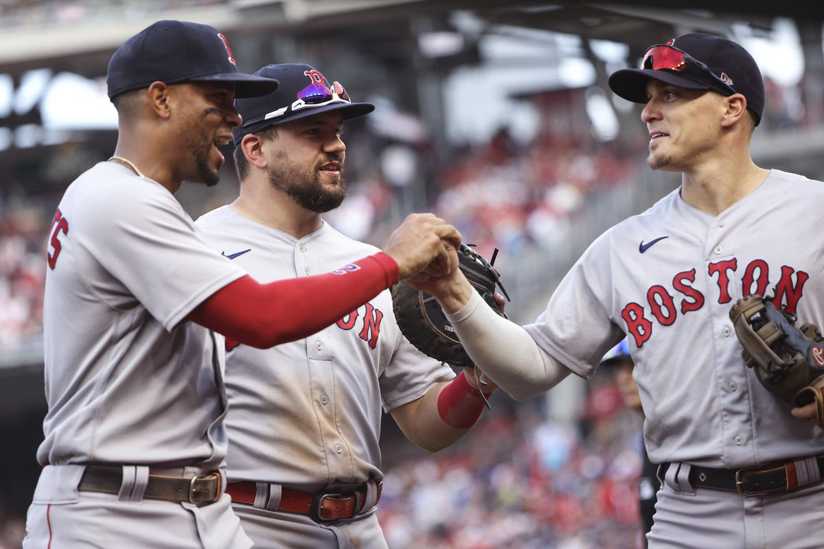 Xander Bogaerts #2, Kyle Schwarber #18 and Enrique Hernandez #5 of the Boston Red Sox celebrate as they walk off the field against the Washington Nationals at Nationals Park on October 02, 2021 in Washington, DC.