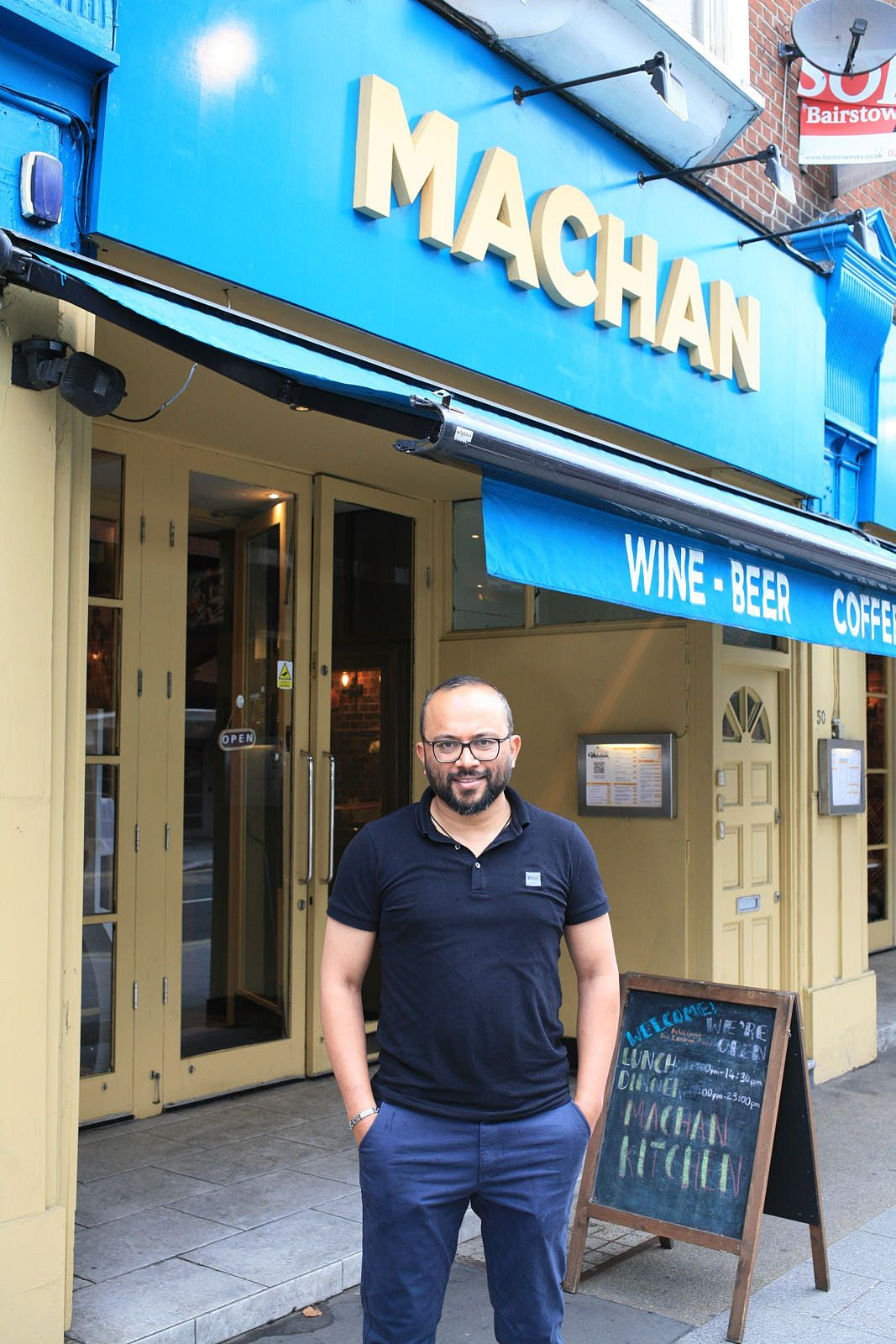 Chef Ratnayaka stands outside his East Croydon restaurant, Machan, which has a large blue frontage with its name in white capital letters.