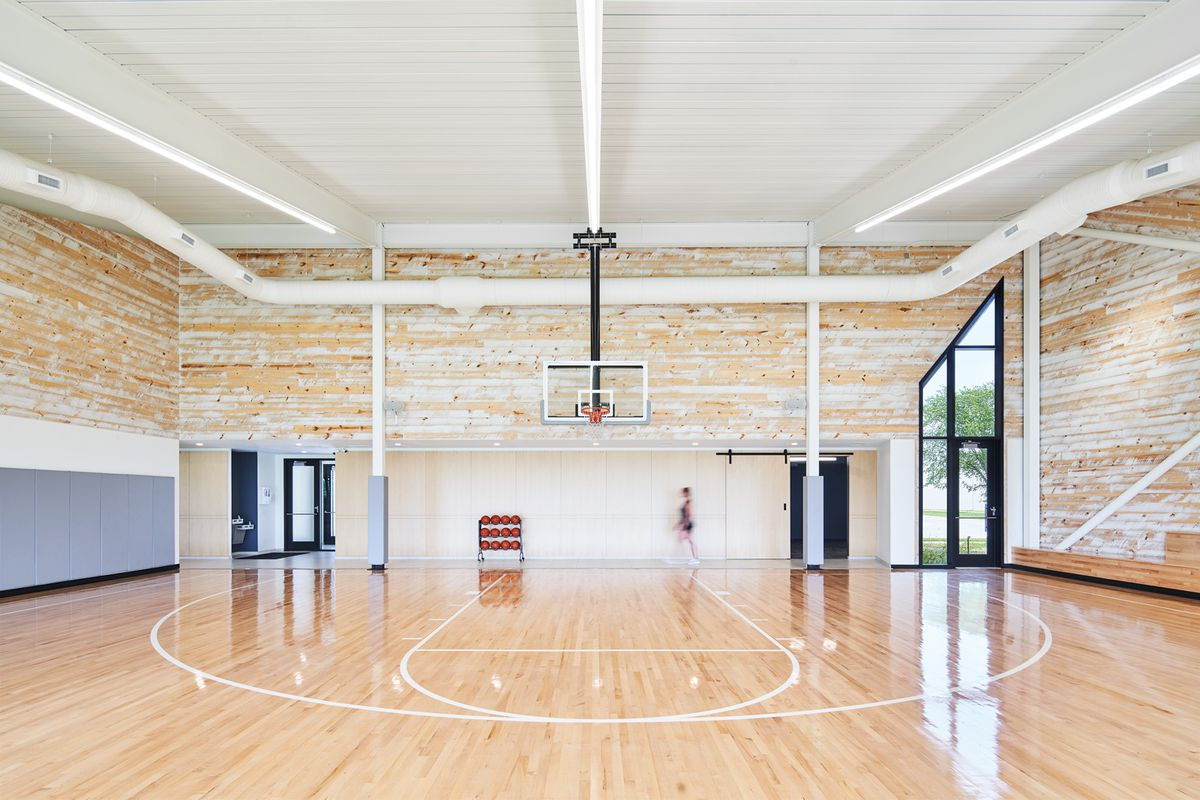 An indoor basketball with white-washed wood walls and a white painted ceiling