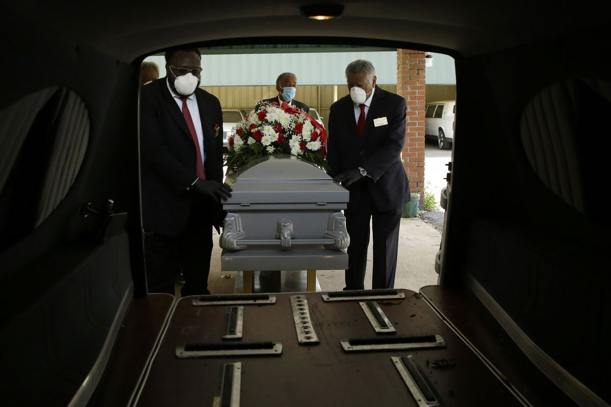 In this Saturday, April 18, 2020 photo, mortician Cordarial O. Holloway, foreground left, funeral director Robert L. Albritten, foreground right, place a casket into a hearse in Dawson, Ga.
