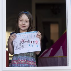 Josephine Hope Anderes holds up a picture she drew of herself social distancing, Thursday, April 30, 2020.