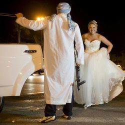 In this Sunday, Aug. 26, 2012 picture, A Romanian bride walking to a limousine as a mock kidnapper holding a toy weapon holds the door for her at the Triumph Arch in Bucharest, Romania. The arch, a replica of the Arc de Triomphe in Paris, the French capital, is a rendezvous place for brides on the wedding night for the bride stealing ritual. The ancient Romanian tradition of bride stealing is getting bigger, brasher and an increasingly common sight in the Romanian capital, the region's undisputed party town.