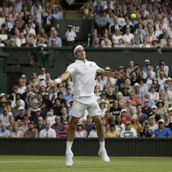 Switzerland's Roger Federer returns the ball to Japan's Kei Nishikori during a men's quarterfinal match on day nine of the Wimbledon Tennis Championships in London on July 10, 2019.