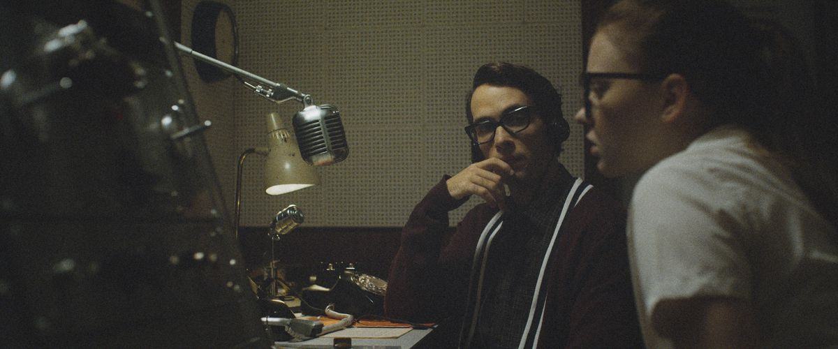 Jake Horowitz and Sierra McCormick sit in front of a 1950s microphone at the radio station in The Vast of Night
