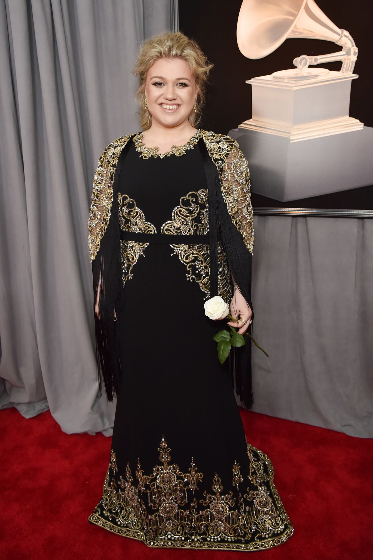 Kelly Clarkson wearing Christian Siriano and carrying her white rose at the 2018 Grammys.