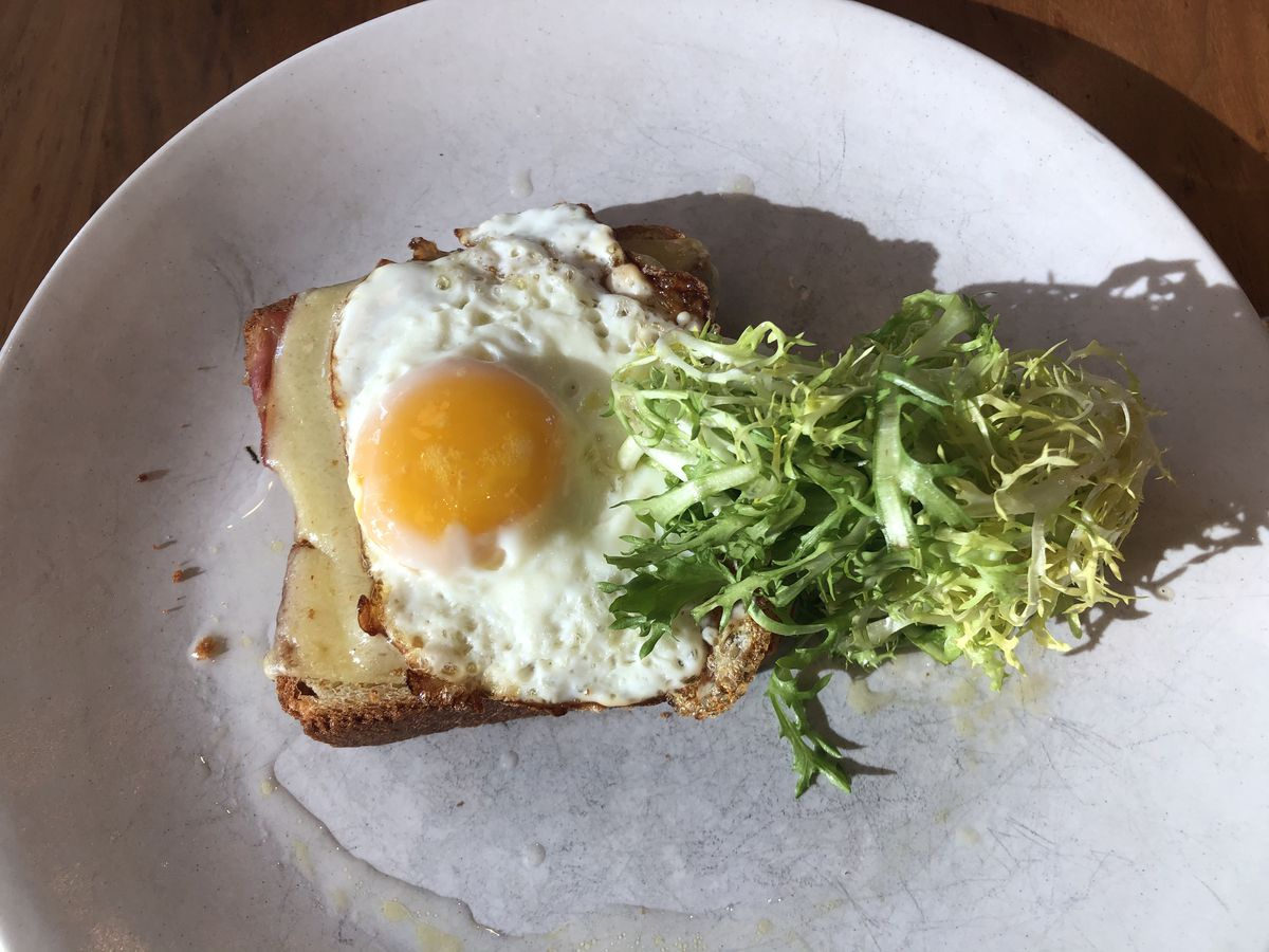 Croque madame on a plate with a pile of lettuce.