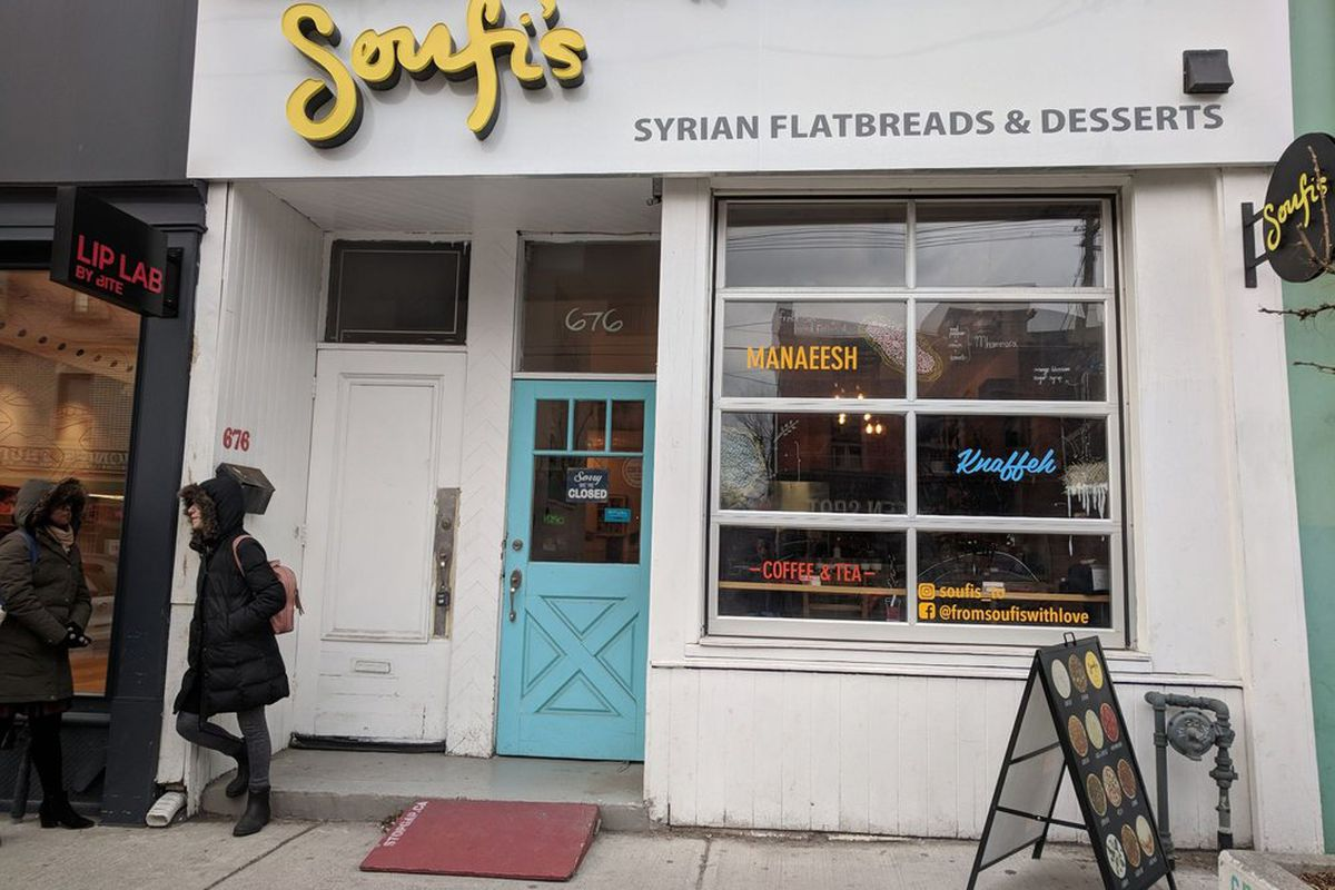 """Exterior of Soufi's restaurant, with sign in yellow reading """"Soufi's,"""" and below it """"Syrian restaurant and desserts"""""""