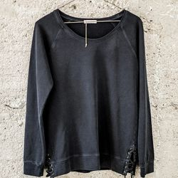 Faded black lace-up sweater.