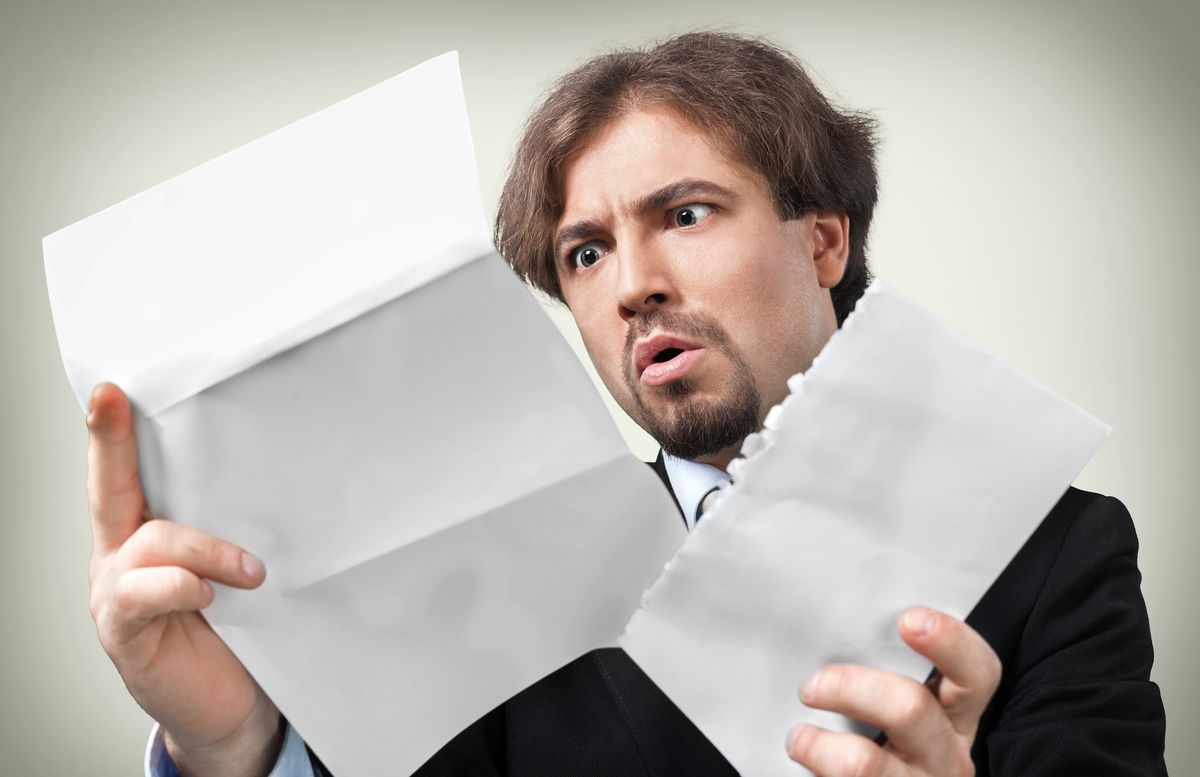Man opening letter and looking astonished