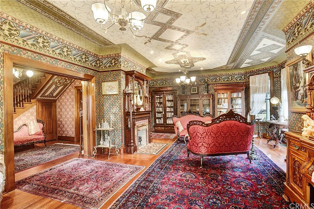 Living room with ornate ceiling, 1800s period furniture, and lots of rugs.