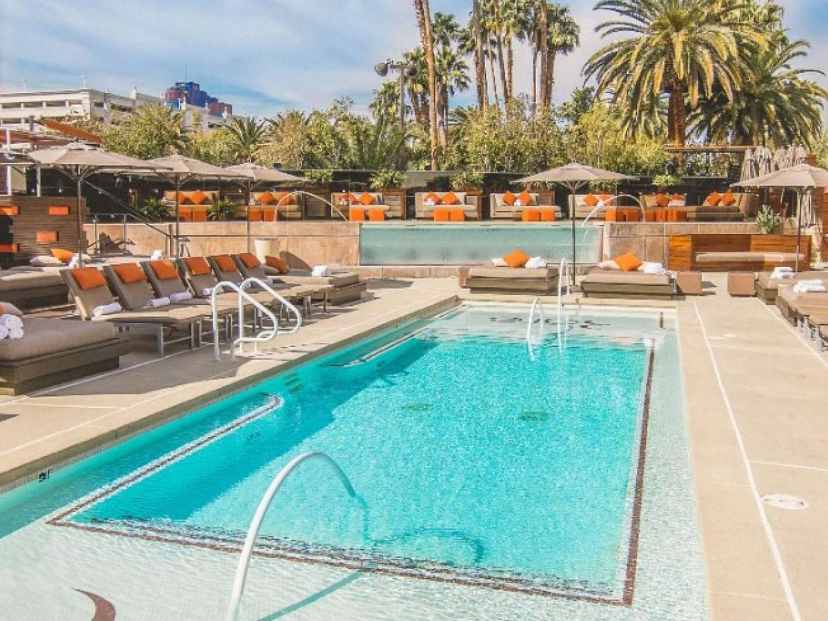 """<span data-author=""""4336141"""">Rectangular pool surrounded by lounge chairs with orange pillows</span>"""