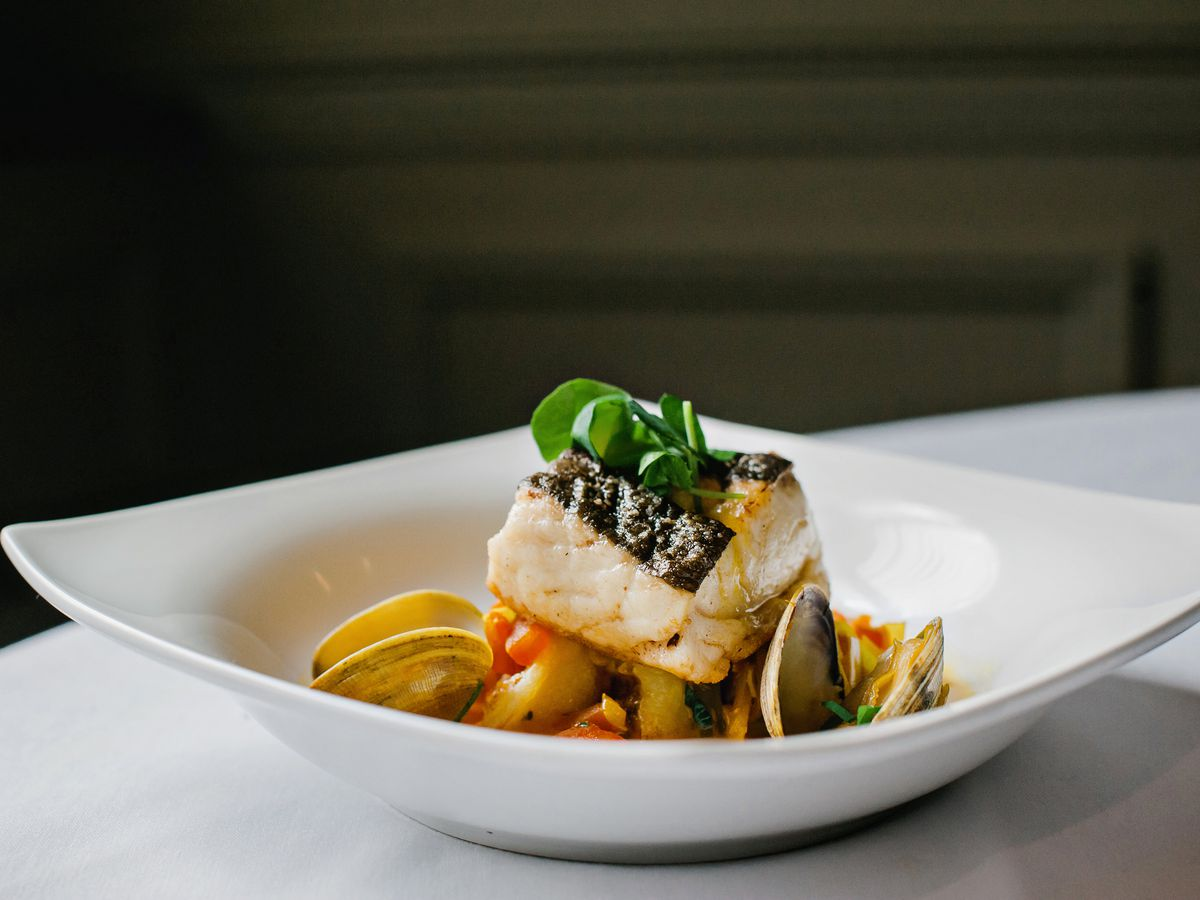 Codfish loin sits in a white bowl, garnished with mussels and other accoutrements. The bowl is on a white tablecloth on a dark background.